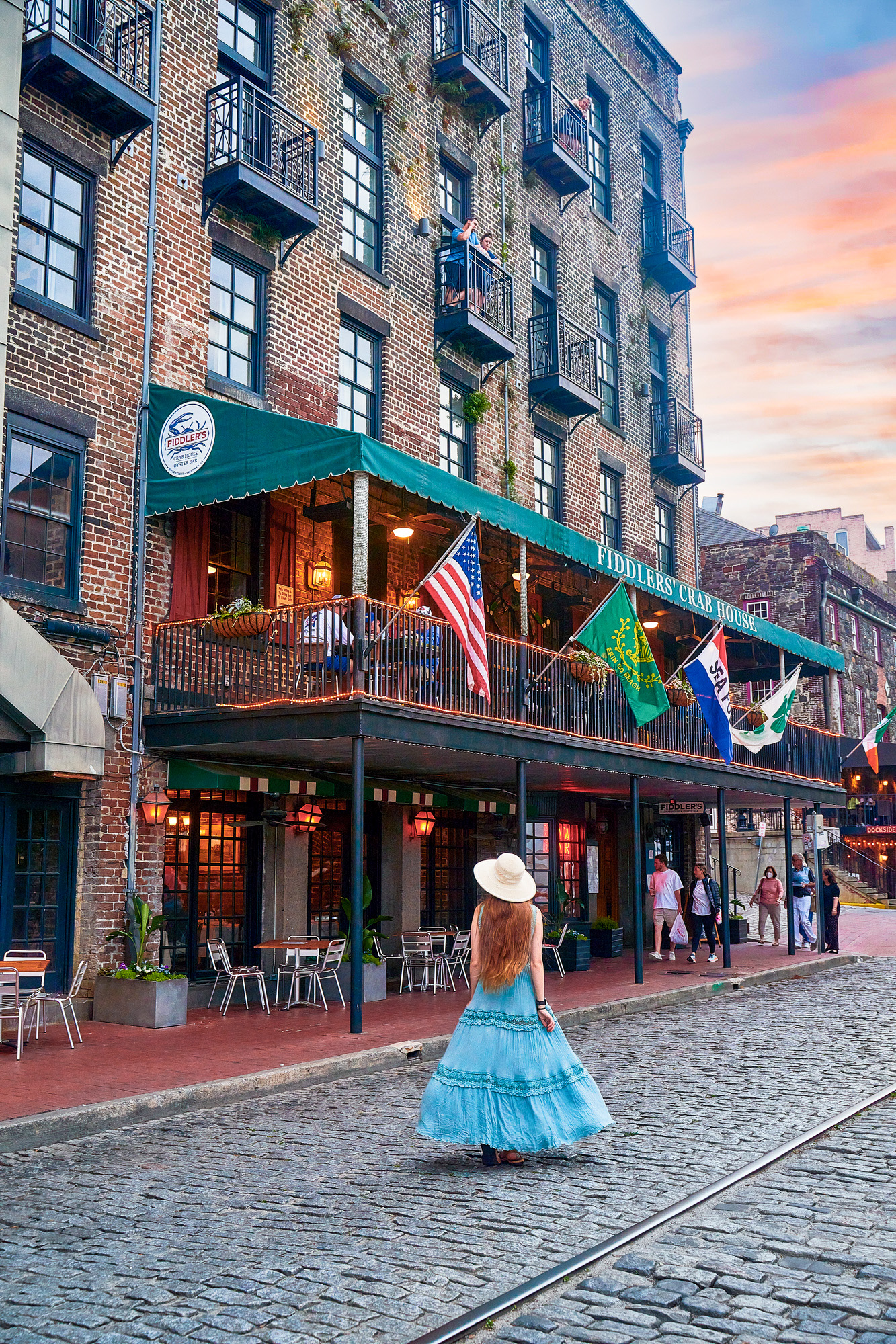 Photo of a girl walking down River Street, which is where to stay in Savannah for entertainment and nightlife.