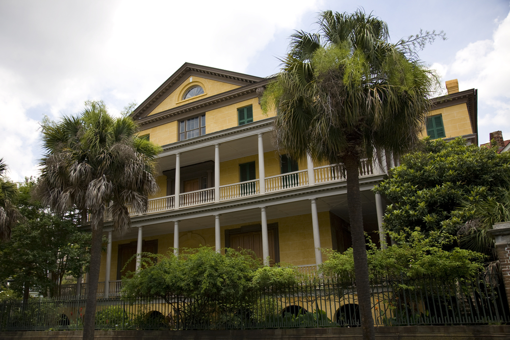 The exterior of the Aiken-Rhett House. The house is yellow with a large front porch and a large front deck. The house is surrounded by palm trees and shrubs.