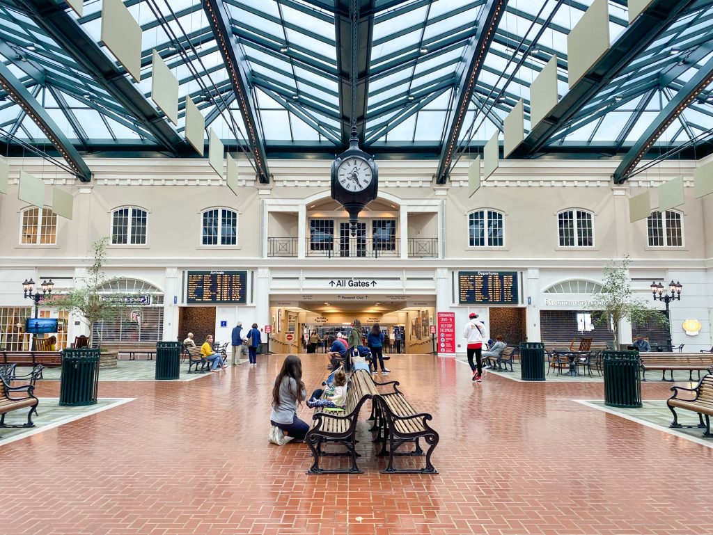 """The lobby of the small airport in Savannah Georgia. It has wrought iron and wood slat benches, a glass ceiling, and an antique style clock hanging from the ceiling. The walls are white and cream and made to look like a small village. There are people walking to a hallway leading to """"All Gates"""" as well as people sitting on the benches. Big screens on the wall show departures and arrivals."""