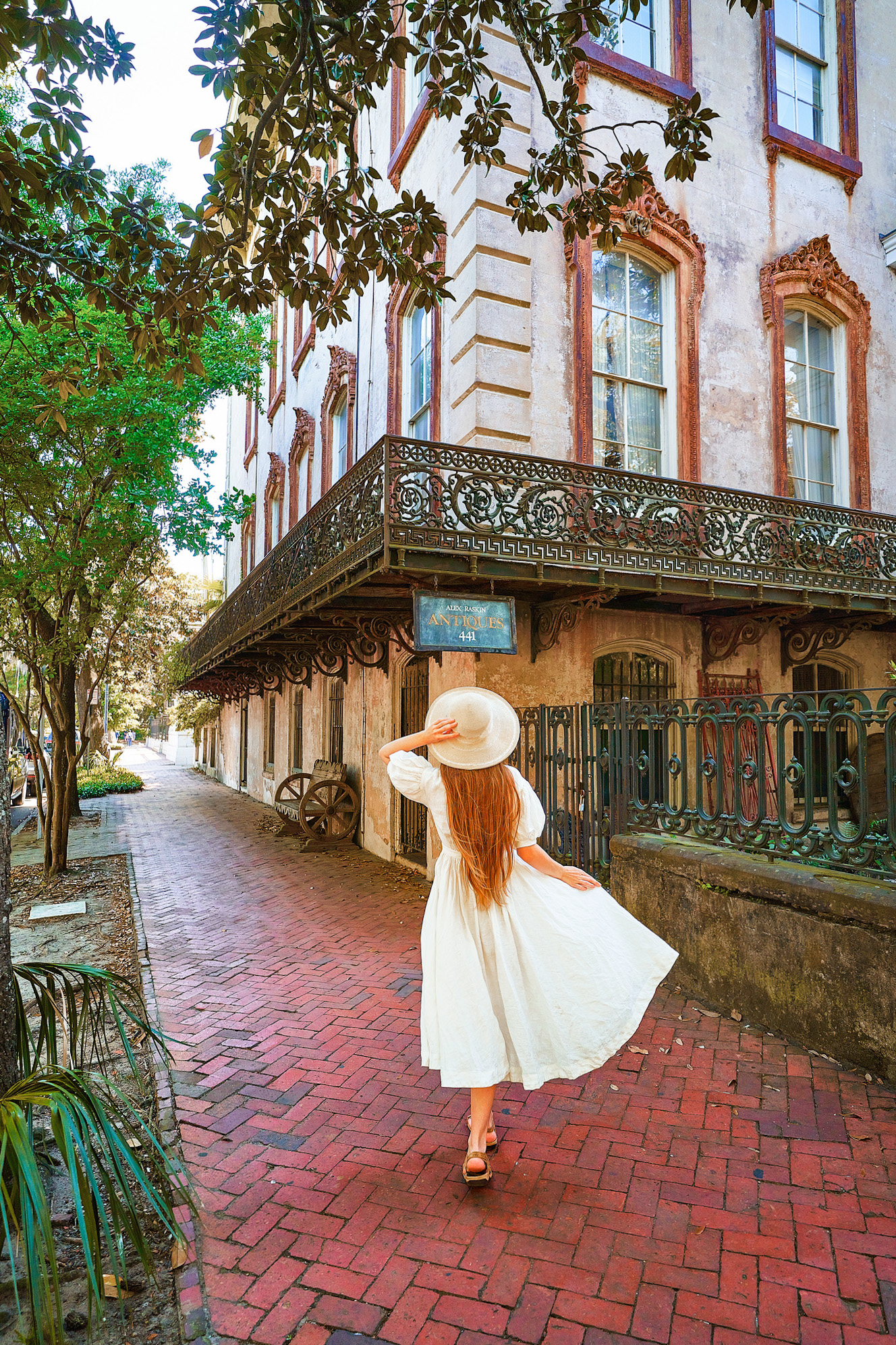 A woman in a white sundress with long hair and a white sunhat standing outside of a run down mansion. She is standing on a brick sidewalk looking up at the building. The building has stained plaster, rusted window trimmings, and a rusted wrought iron balcony and gate.