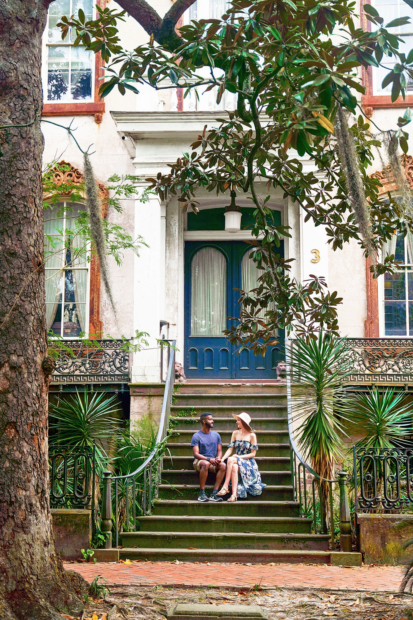 A couple sitting on the stone steps in front of the Alex Raskin Antique store in Savannah Georgia. The steps are surrounded by greenery and lead to double doors with large windows that are painted blue. The building is old and painted white with rust colored trim. The woman in the couple is wearing a blue floral sundress with a sunhat. The man in the couple is wearing a blue shirt and khaki shorts. They are facing each other on the steps and holding hands. A haunted and cool building you perfect for Savannah photo spots
