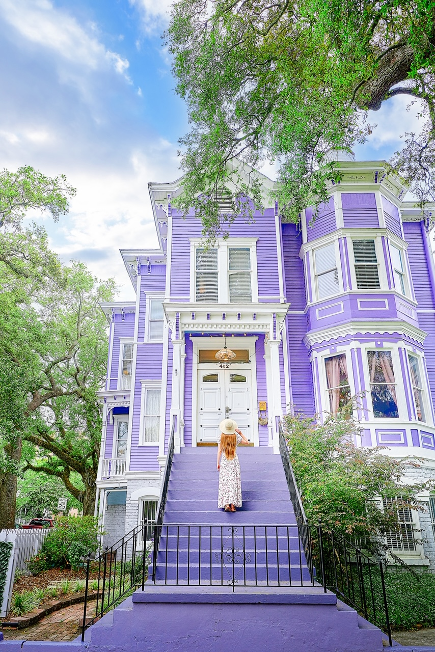 The exterior of a large Victorian mansion that is a bright pastel purple. It has white trimmings, a large set of white double doors, and the stairs leading up to the entrance to the house are also painted purple. There is a woman with long hair in a white floral maxi dress and a white sun hat standing on the steps. The house is surrounded by trees and shrubs.