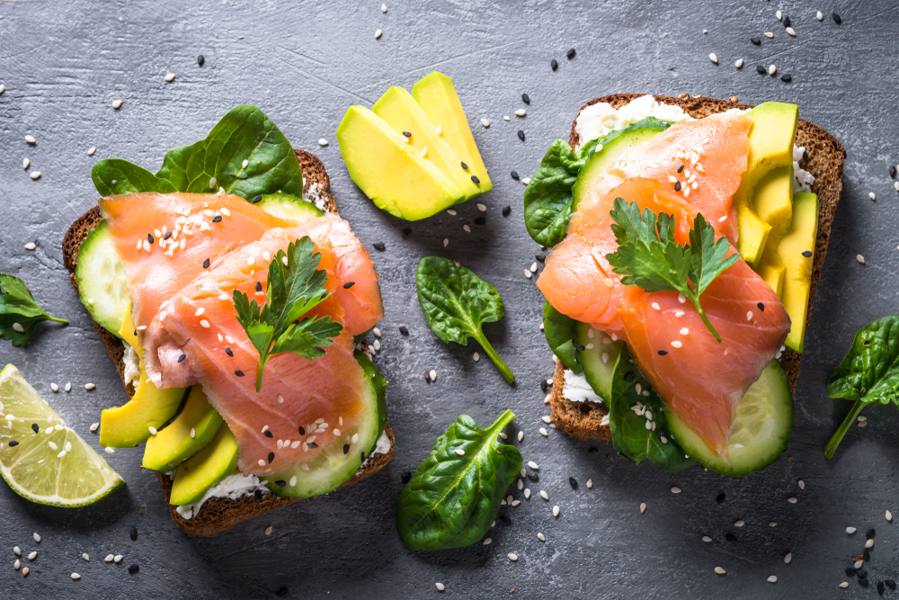 A plate of avocado toast with cucumbers, spinach, lox, and sesame seeds on it. It is on a black plate and there or lime wedges near it.