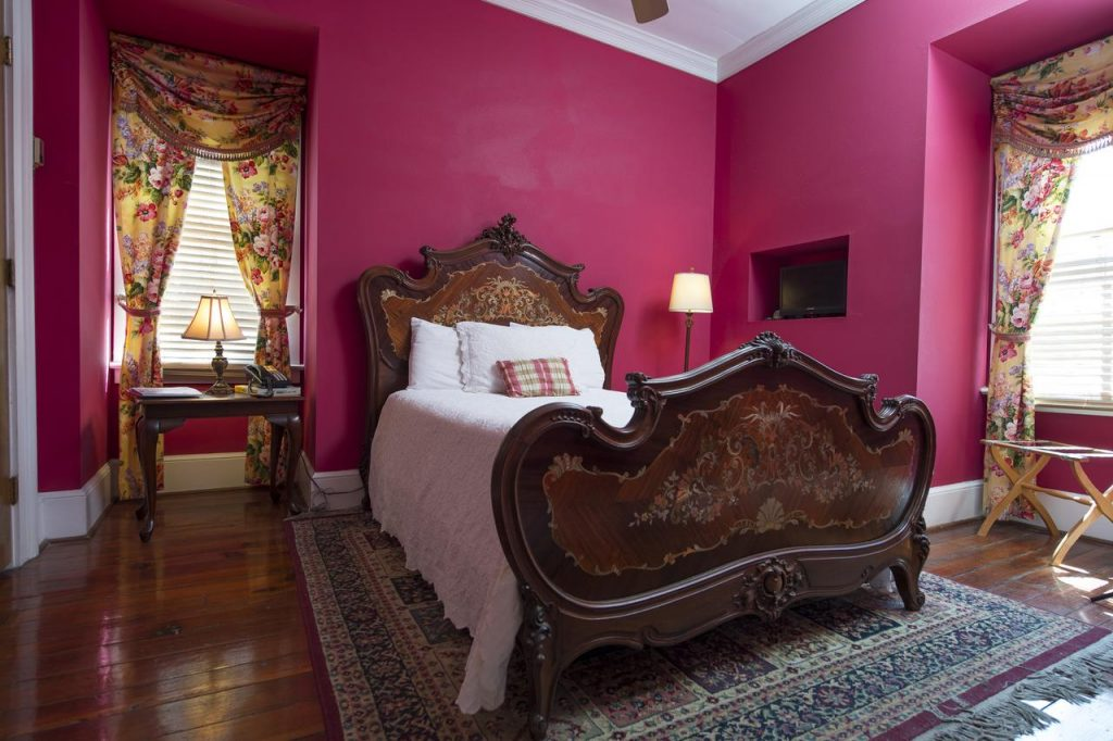 An opulently decorated bedroom with fuchsia walls, a large and ornately painted bed, and floral curtains on the two windows. There is an oriental rug under the bed, its a great place to stay during a weekend getaway in Charleston