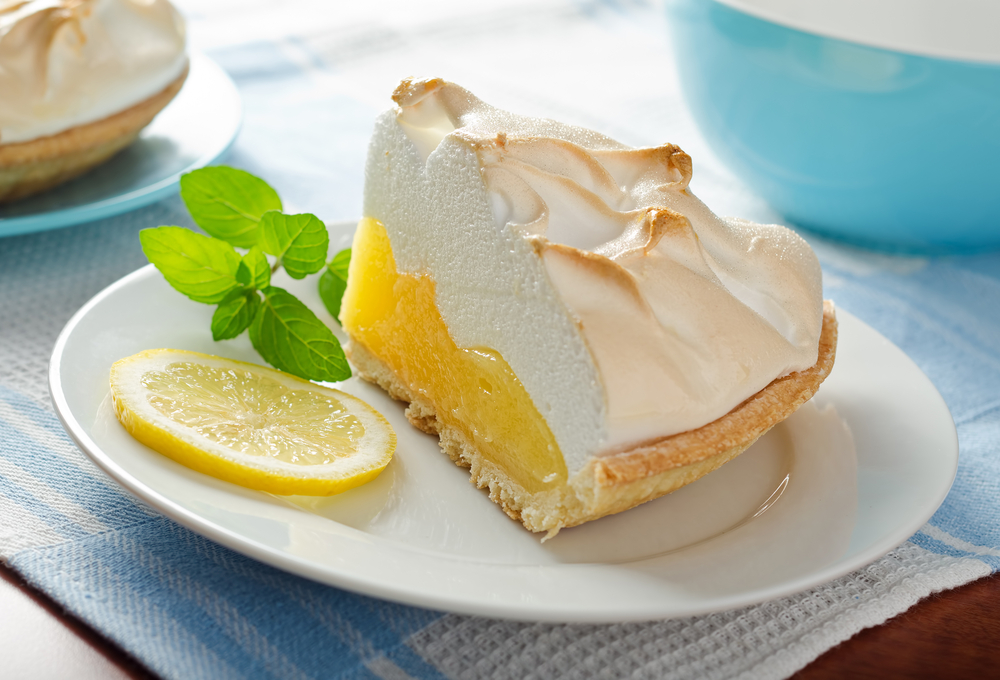 lemon meringue pie on a plate with a sprig of mint
