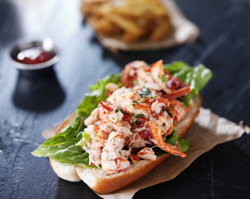 lobster roll on a parchment paper laying on a black counter