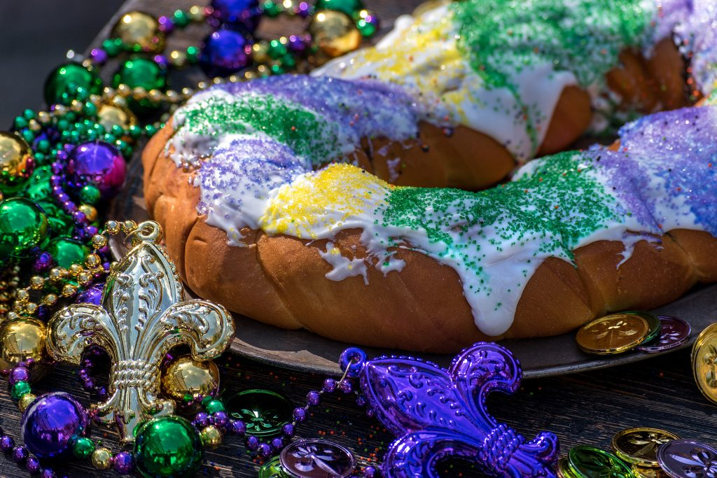 A King cake is topped with green, yellow, and purple sprinkles, the signature colors of Mardi Gras