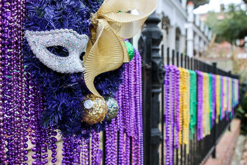 Beads hang from a fence along with masks during Mardi Gras, the best time to visit New Orleans