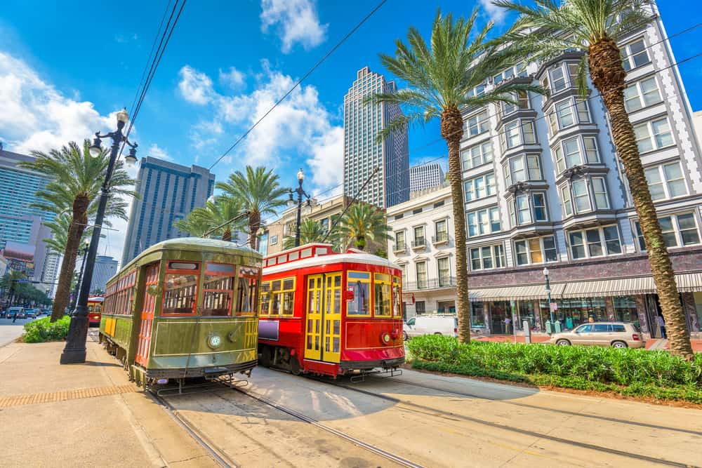 Two colorful streetcars drive through downtown New Orleans.