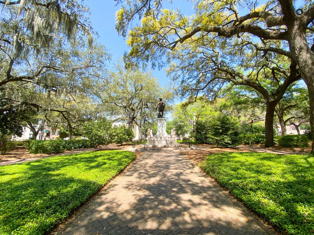 The view of one of the squares on Bull Street in Savannah.  It has sidewalks surrounded by grass leading up to a statue. The statue is a large metal statue of a man on a large white pedestal. There are a lot of trees and shrubs surrounding the square. A great place to see on your 3 days in Savannah trip