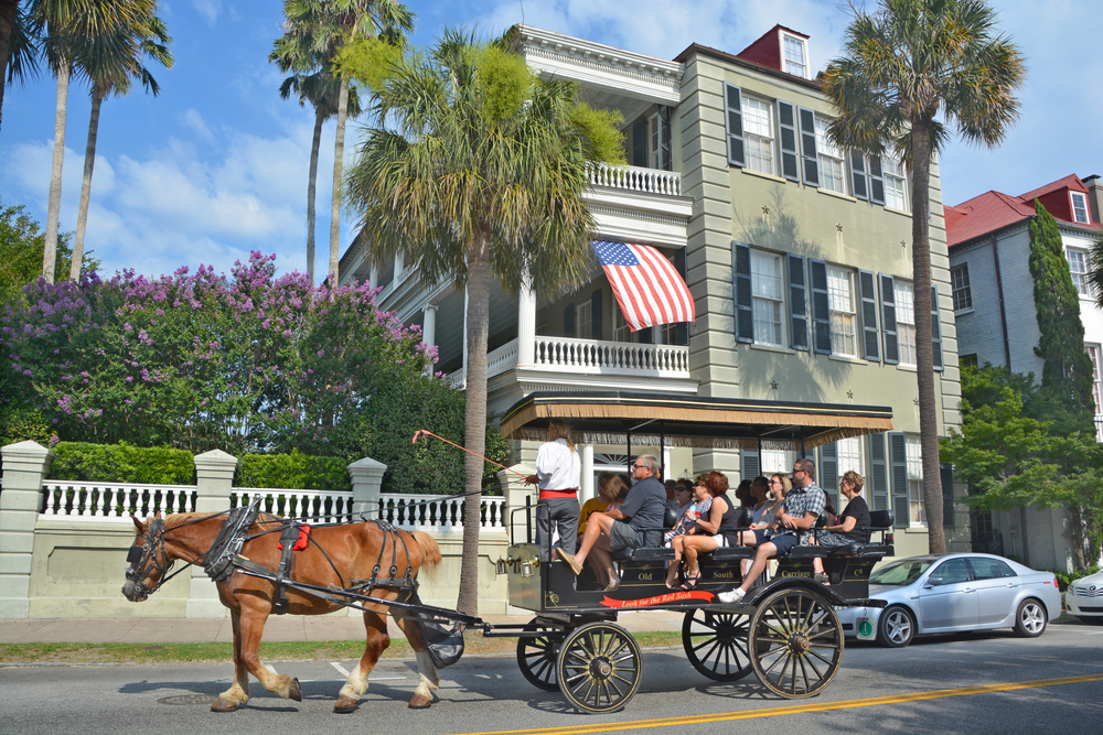 People in a covered carriage being driven by a horse in front of a historic house in Charleston South Carolina. The house is green and there are palm trees and a lilac bush in front of it. A great way to explore a weekend in South Carolina