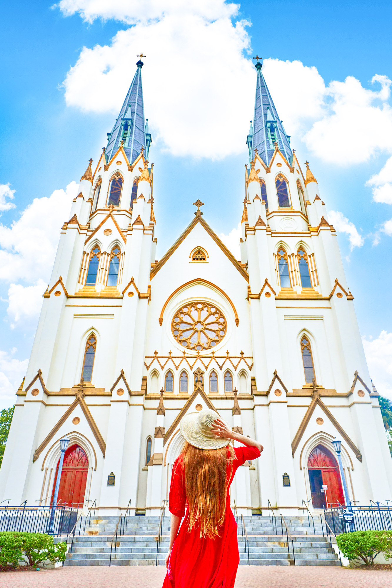 A woman standing in a bright red dress with her long hair down and wearing a cream colored sun hat looking up at the Cathedral Basilica of St. John The Baptist. The Cathedral is very large and cream with an intricate Gothic Revival architectural design. The trimmings of the church are gold and there are two large arched doors on either side of the building that are bright red.