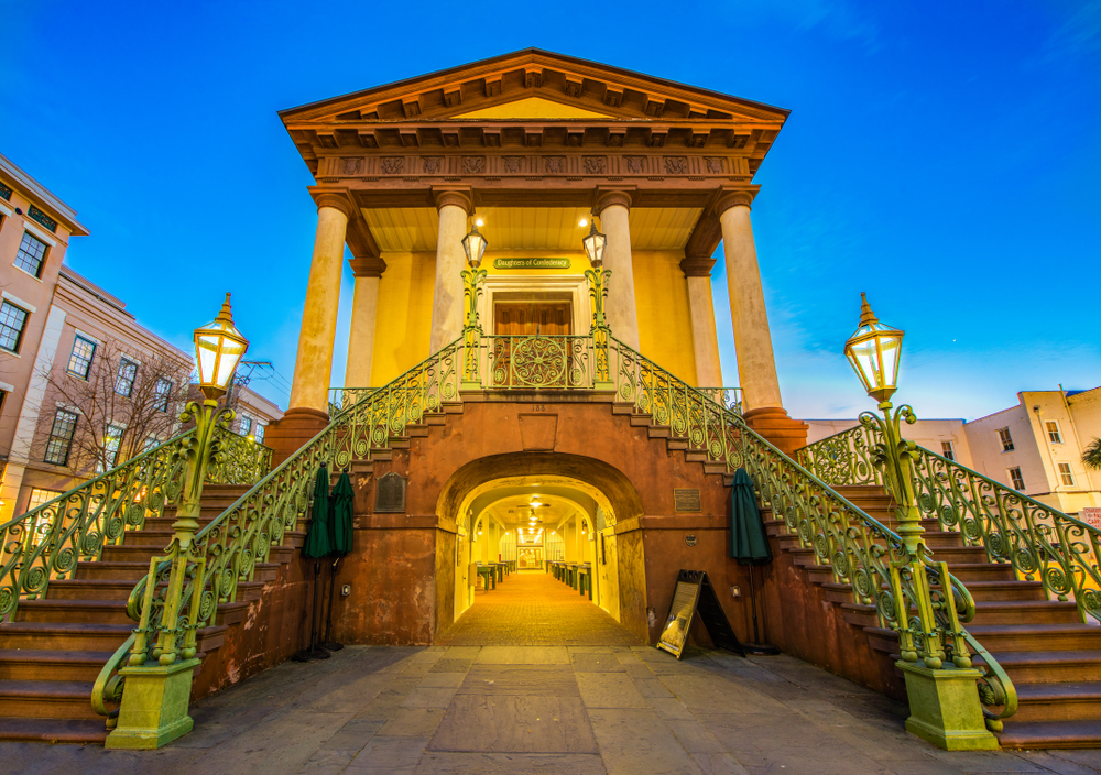 The entrance to the Charleston City Market in downtown Charleston. The entrance has two large staircases on either side leading to the main doors. It is sunset, so the building is glowing yellow and all lit up.