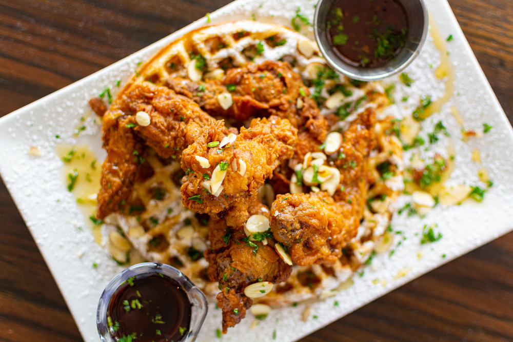 A plate of fried chicken over waffles. There are toppings on it like scallions and nuts. There are also two dipping sauces on the rectangular white plate. The plate is on a wood table.