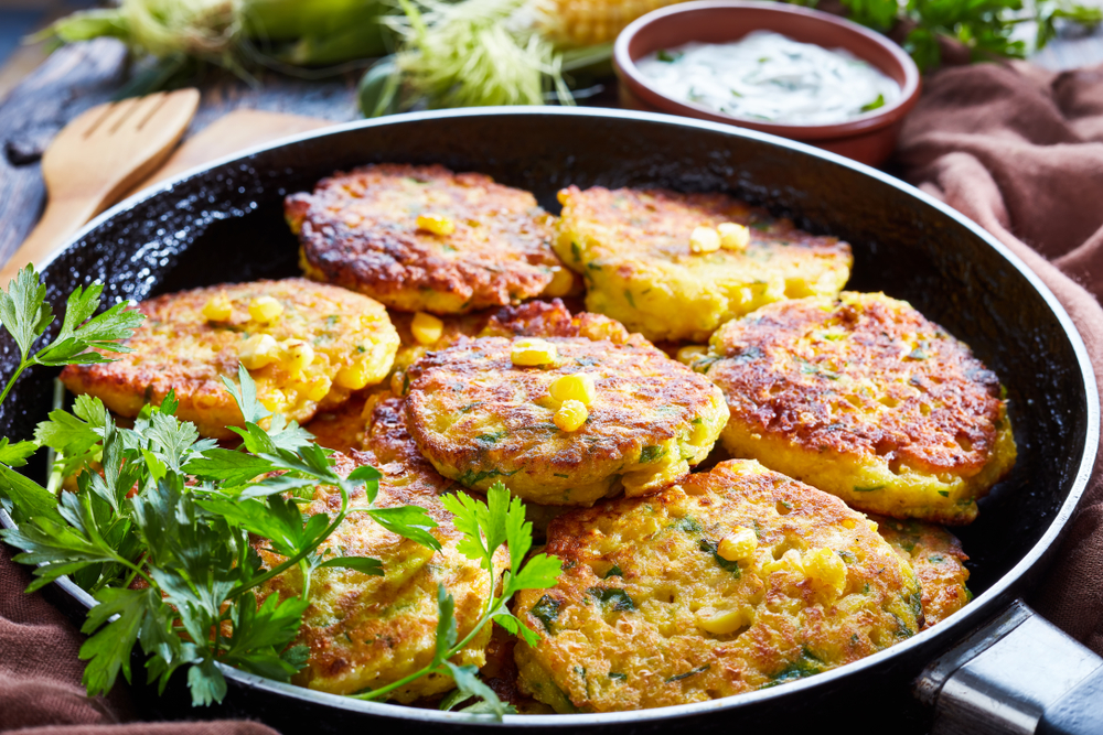 A pan of corn fritters with some greenery on the side. In the background there are cooking utensils like a wooden spatula, a bowl of sauce, and a cloth napkin