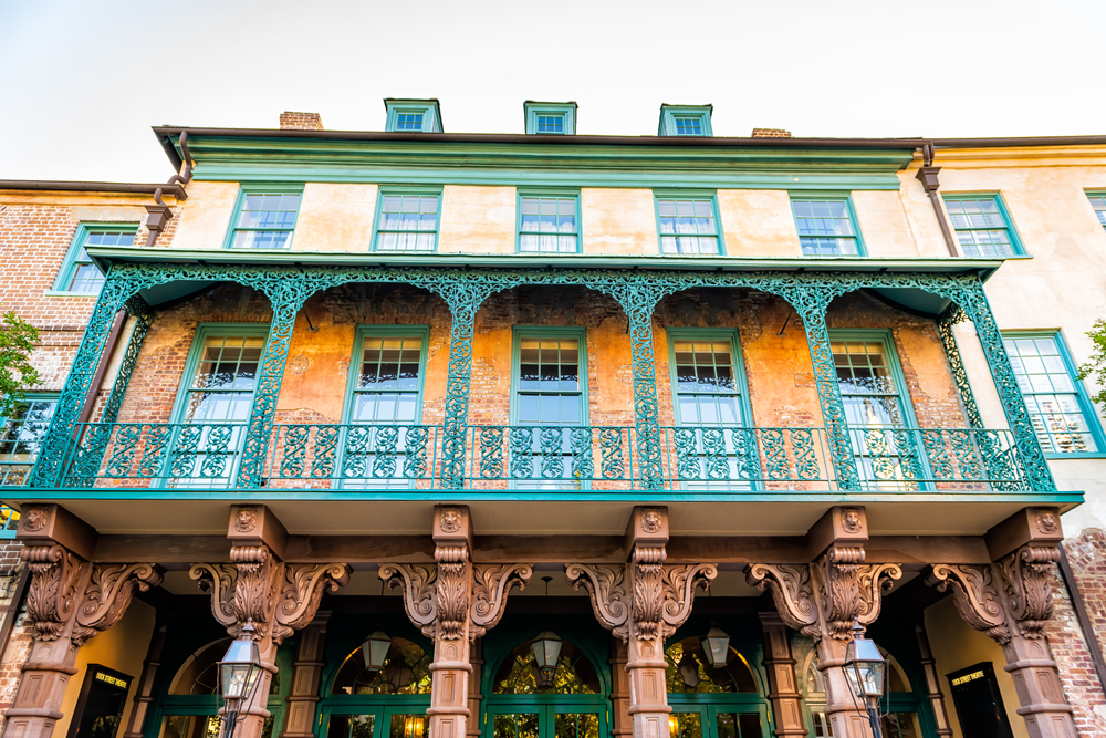 The exterior of the top of the Dock Street Theater. There is intricate iron work on the patio that is painted green. The building is brick and plaster with the plaster painted an orange color. The window trimmings are painted green.