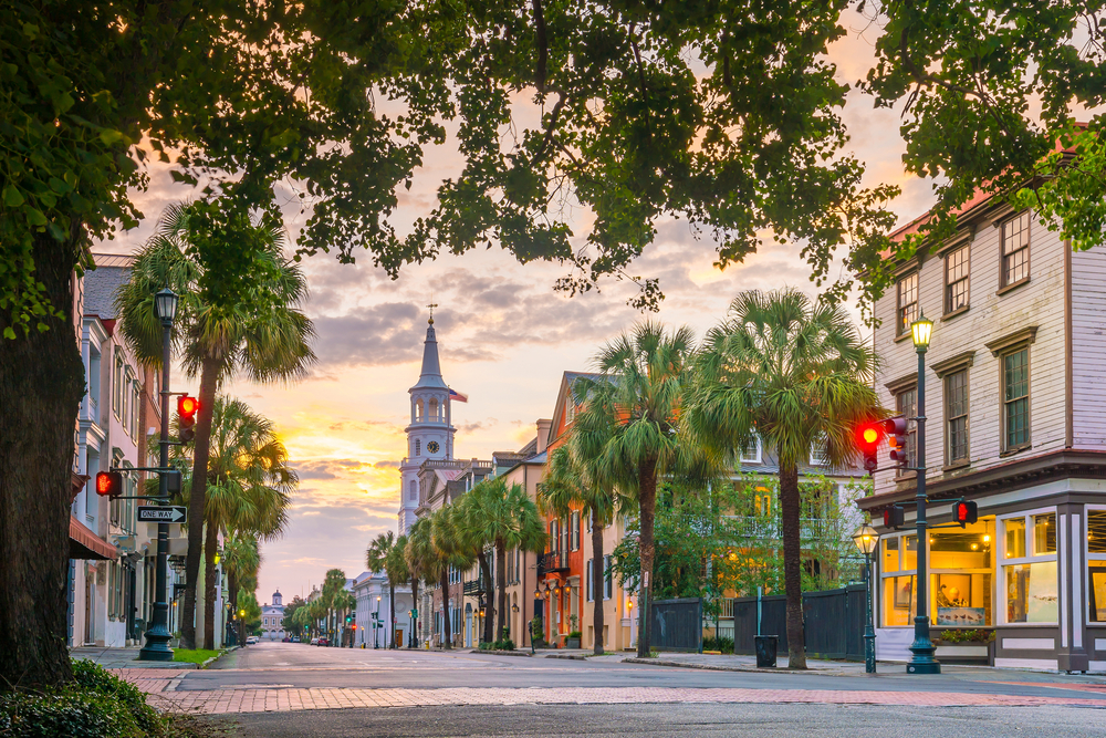 The view of downtown Charleston South Carolina at sunset. There are rows of palm trees, a tall bell tower on a church, and shops and homes along the road.