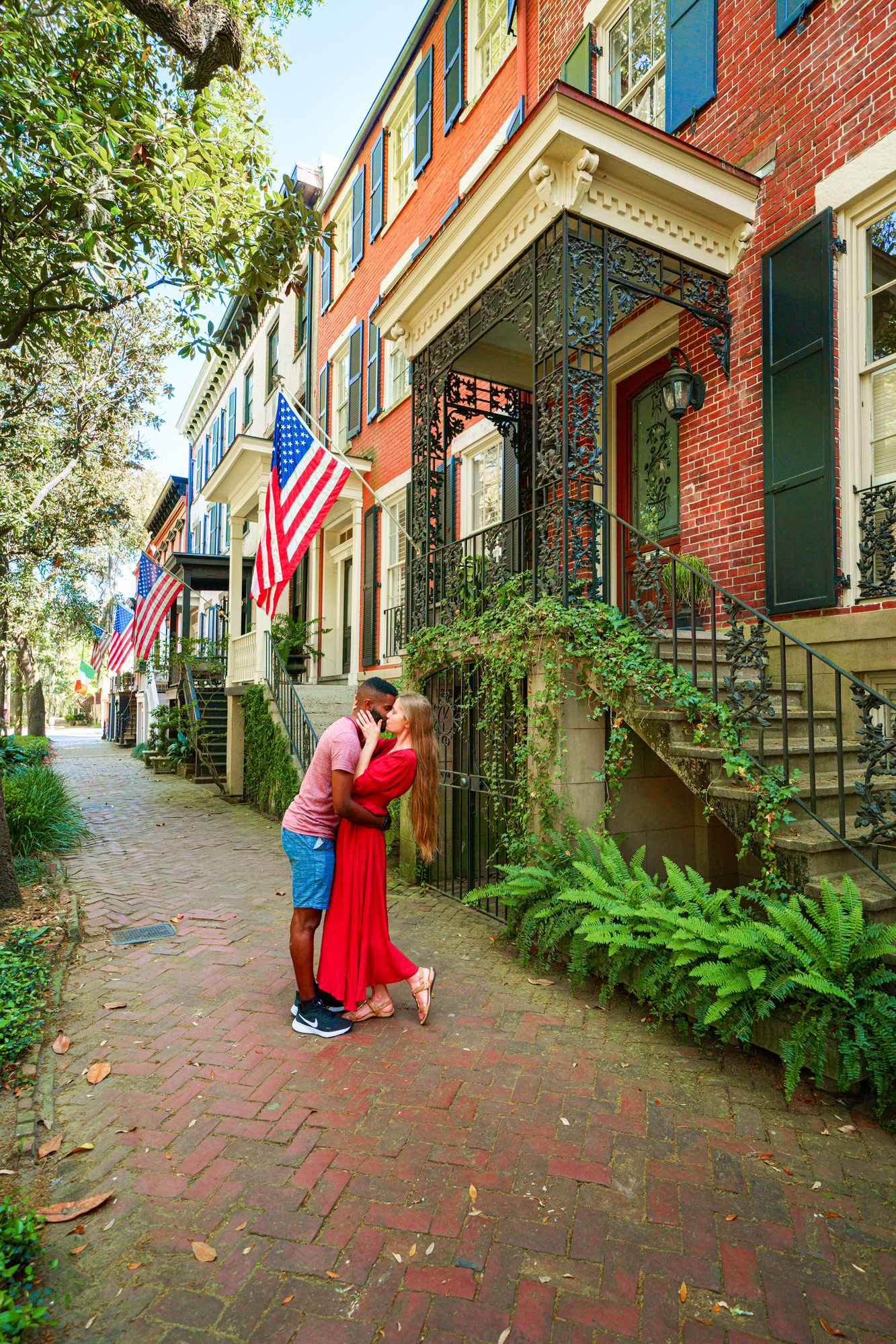A couple standing and kissing on East Jones Street in Savannah. The street is lined with historic homes hanging American flags. It is a cobblestone sidewalk and there are trees on the other side. The house closest to the couple is brick with wrought iron stairs and overhang that is covered in vines. The woman in the couple is wearing a red dress and her long hair is down. The man in the couple is wearing a red heather shirt with denim blue shorts.
