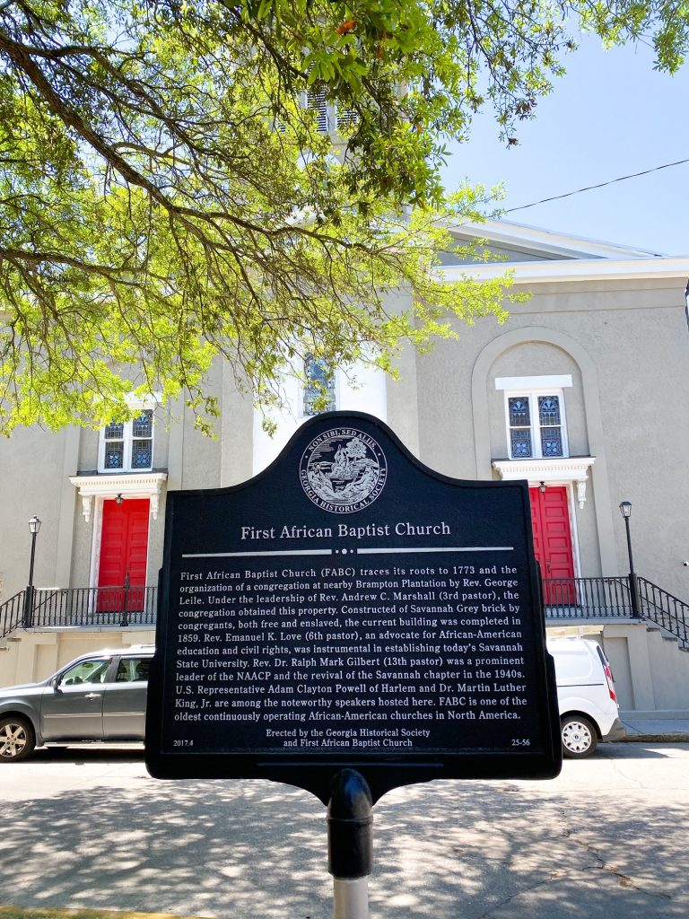 A large black plaque on the sidewalk in front of the First African Baptist Church. It details the history of the church. Behind the sign you can see a large grey building with stained glass windows with white trim and two sets of large red doors. There is a tree that is hanging over the black sign.
