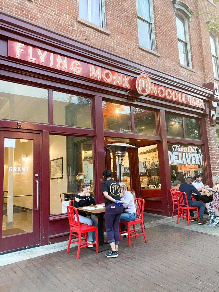 The exterior of the Flying Monk Noodle Bar in Savannah. The building is full of windows with the restaurants logo and an infographic that says 'take out and delivery'. There are people sitting outside of the restaurant and sets