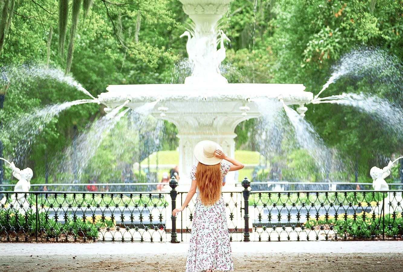 A woman in a white floral long dress, with long hair, and a white sun hat standing in front of the famous Forsyth Fountain. The fountain is very large and has a large middle fountain that has a person standing at the top and water coming out from several places. Behind the fountain are tons of trees with Spanish moss hanging from them. A must see spot during your 3 days in Savannah.