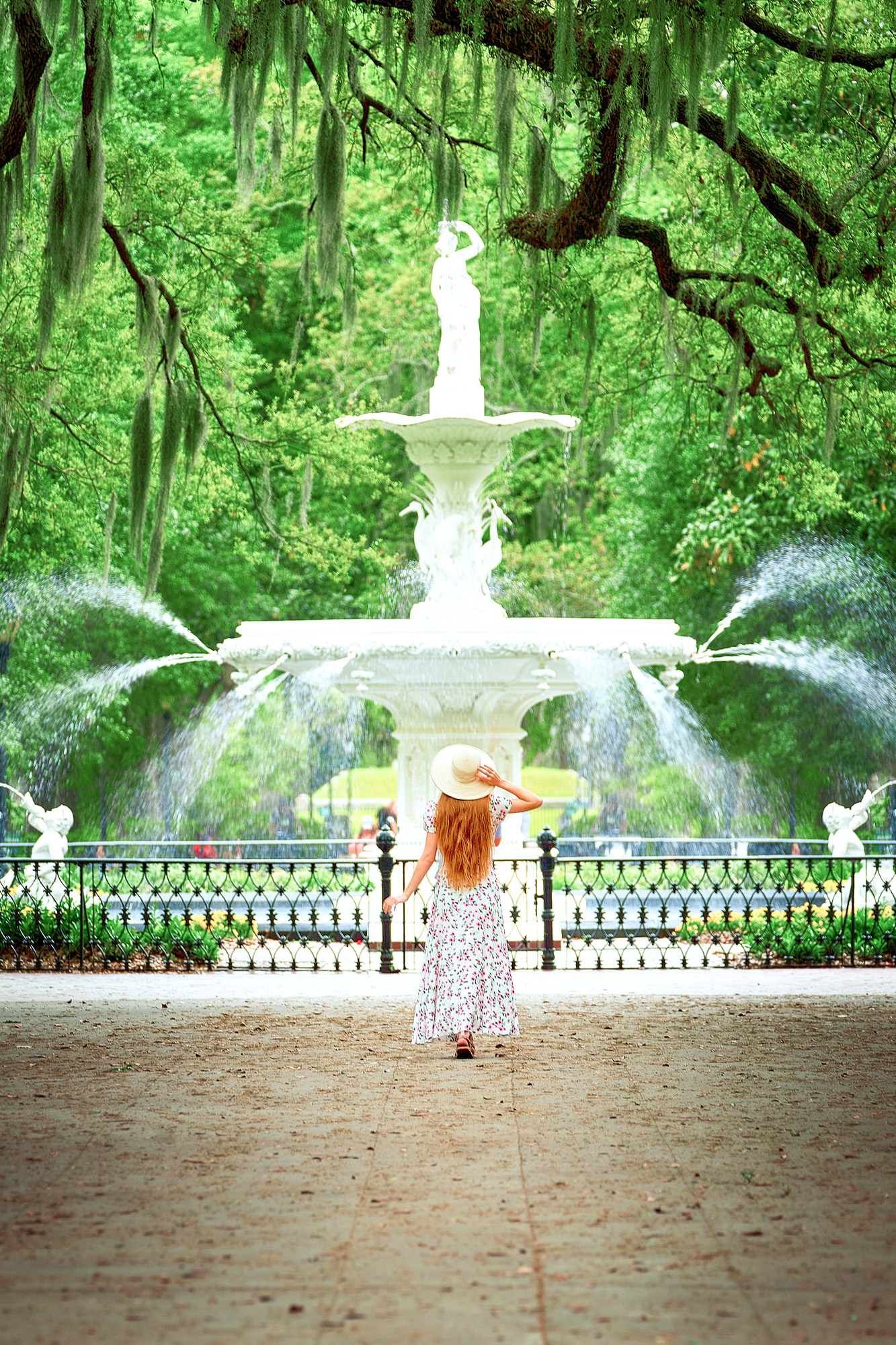A woman in a white long sun dress with long hair and a white sun hat standing in front of the famous Forsyth fountain. Behind it are tons of trees covered in Spanish moss. It is one of the most iconic Savannah photo spots.