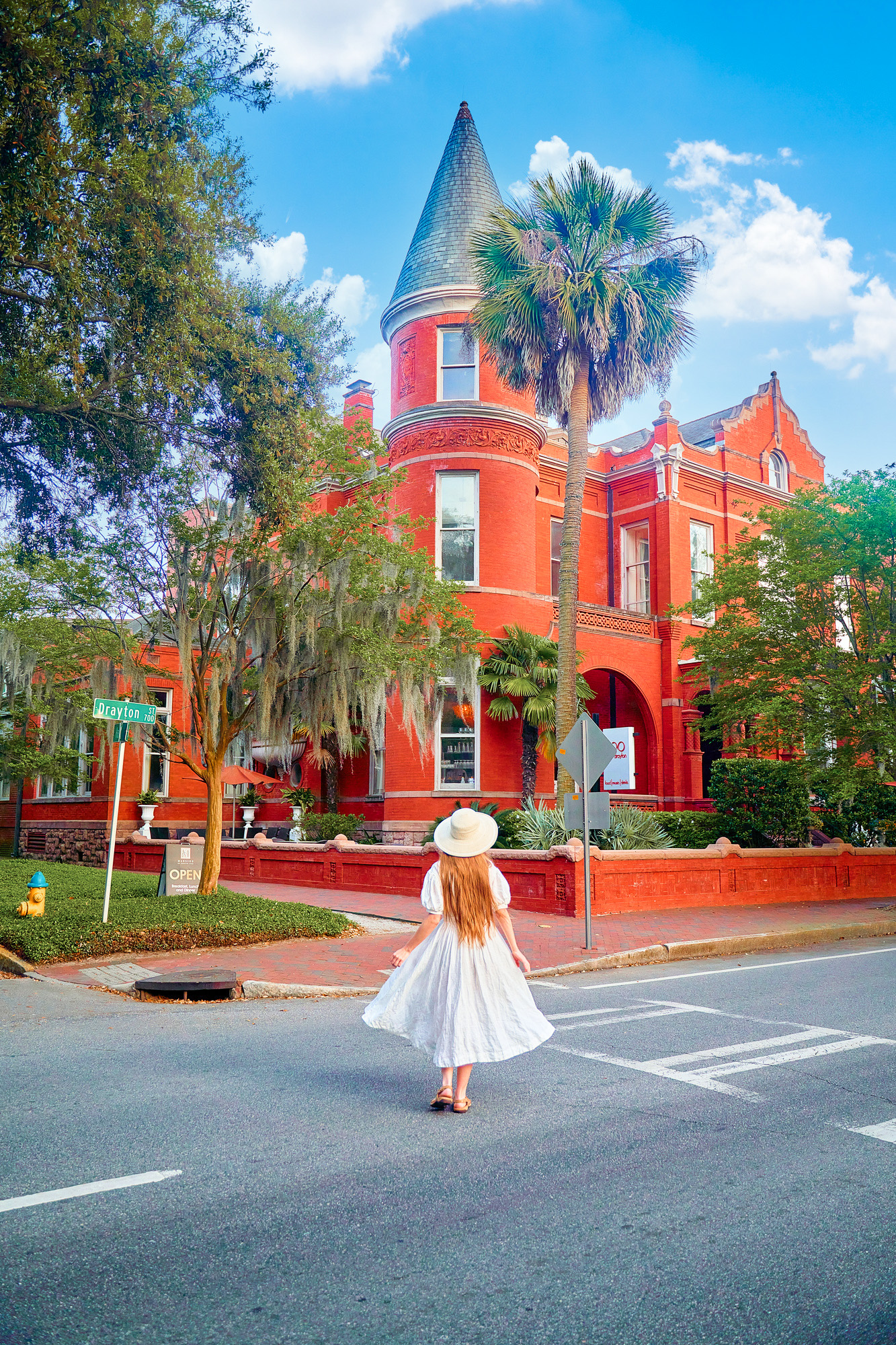 A woman with long hair wearing a white sundress and sun hat standing in the road in front of the Forsyth Mansion. Forsyth Mansion is a large brick home with turrets, lots of windows with white trim, and a courtyard. There are a lot of trees in front of it and shrubs and it is on the corner of the street. One of the best Savannah photo spots.