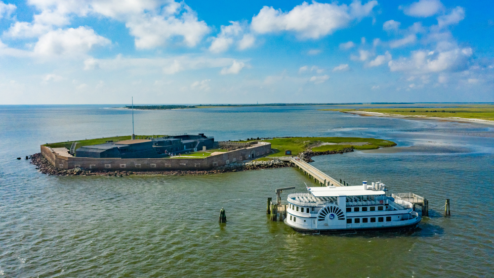 An aerial view of Fort Sumter in South Carolina with a ferry parked outside of it. It is a sunny day with clouds in the sky.