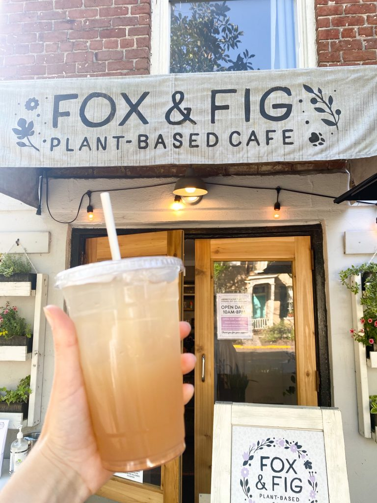 A hand holding a limeade drink with a lid and a straw in front of a store front. The store front is 'Fox & Fig Plant Based Cafe'. There is a large set of wooden French doors that lead inside the cafe. You can see some flower boxes on either side of the door with yellow, pink, and orange flowers. There is also a a standing sign that is painted white with the shops name and logo on it.