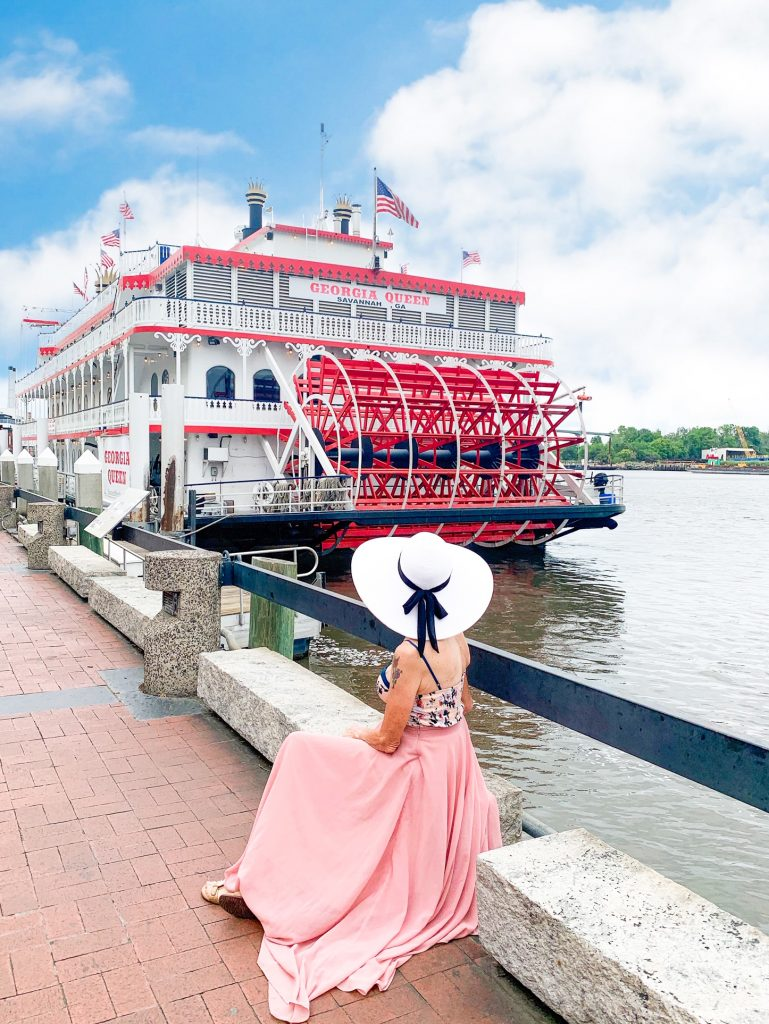 """A woman sitting on a white stone bench next to the Savannah River wearing a pale pink maxi dress, a white floral tank top, and a large white sun hat with a black bow. The woman is facing a large white paddle wheeler boat with red trim called the """"Georgia Queen"""""""