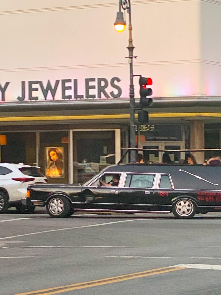 A hearse driving down the street with advertising on the side for ghost tours.