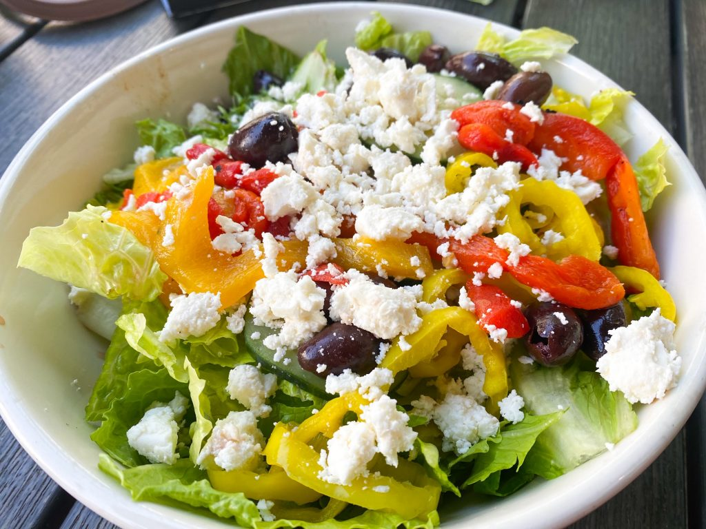A large Greek salad full of romaine lettuce, red peppers, yellow peppers, red onion, olives, picked jalapenos and feta cheese in a white bowl.