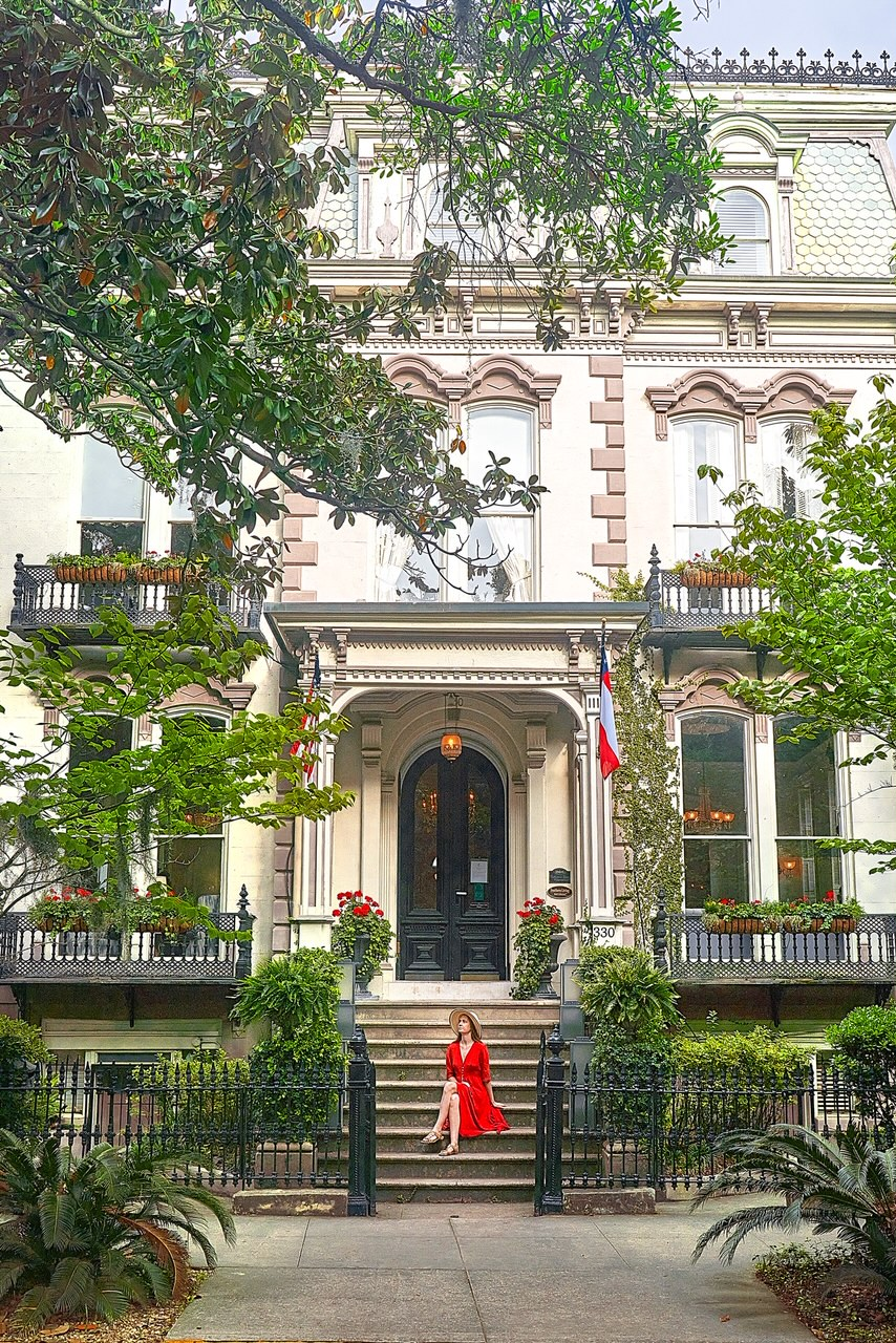 A woman in a red dress and tan sun hat sitting on the steps of the Hamilton Turner Inn. It is a large historic home with Antebellum architectural features. The home is cream with black doors and a black wrought iron fence. It is surrounded by plants in pots like ivy, red flowers, ferns, and palms.