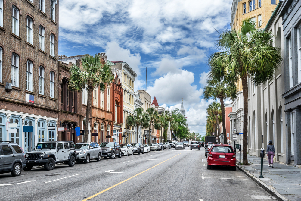 A view of King Street, the most popular shopping street in Charleston. There are lots of historic buildings that have been turned into shops, palm trees, and cars parked on the side of the street. It is a sunny day with big fluffy clouds.