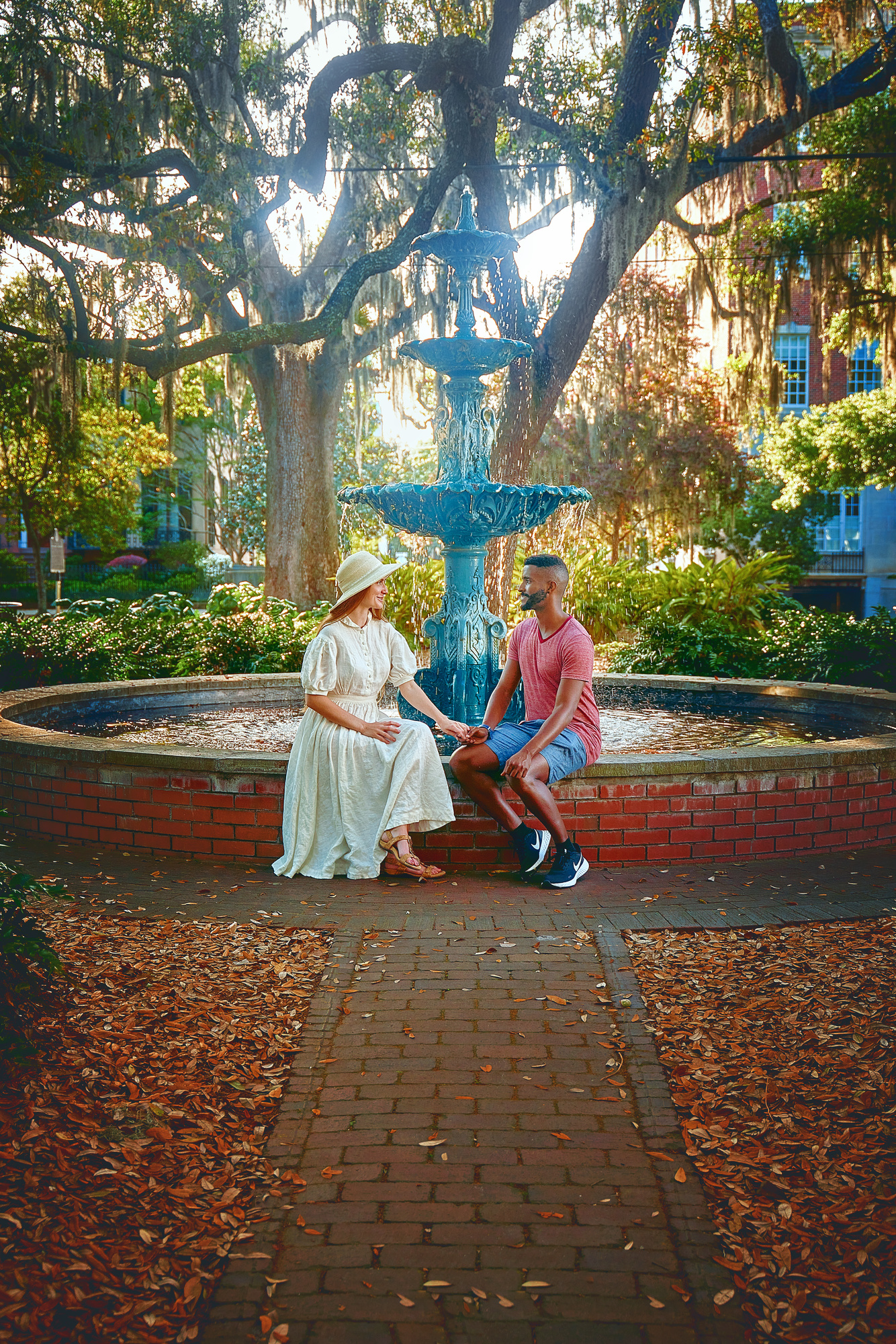 A couple sitting in front of the fountain at Lafayette Square. The Fountain is aged copper, so it is green, and the pool is made of antique brick. Behind the fountain are lots of trees with Spanish moss and shrubs. You can just barely see buildings through the trees. The woman in the couple is wearing a white dress with a white sun hat. The man in the couple is wearing a red heather shirt and denim blue shorts. They are sitting and looking at each other while holding hands.