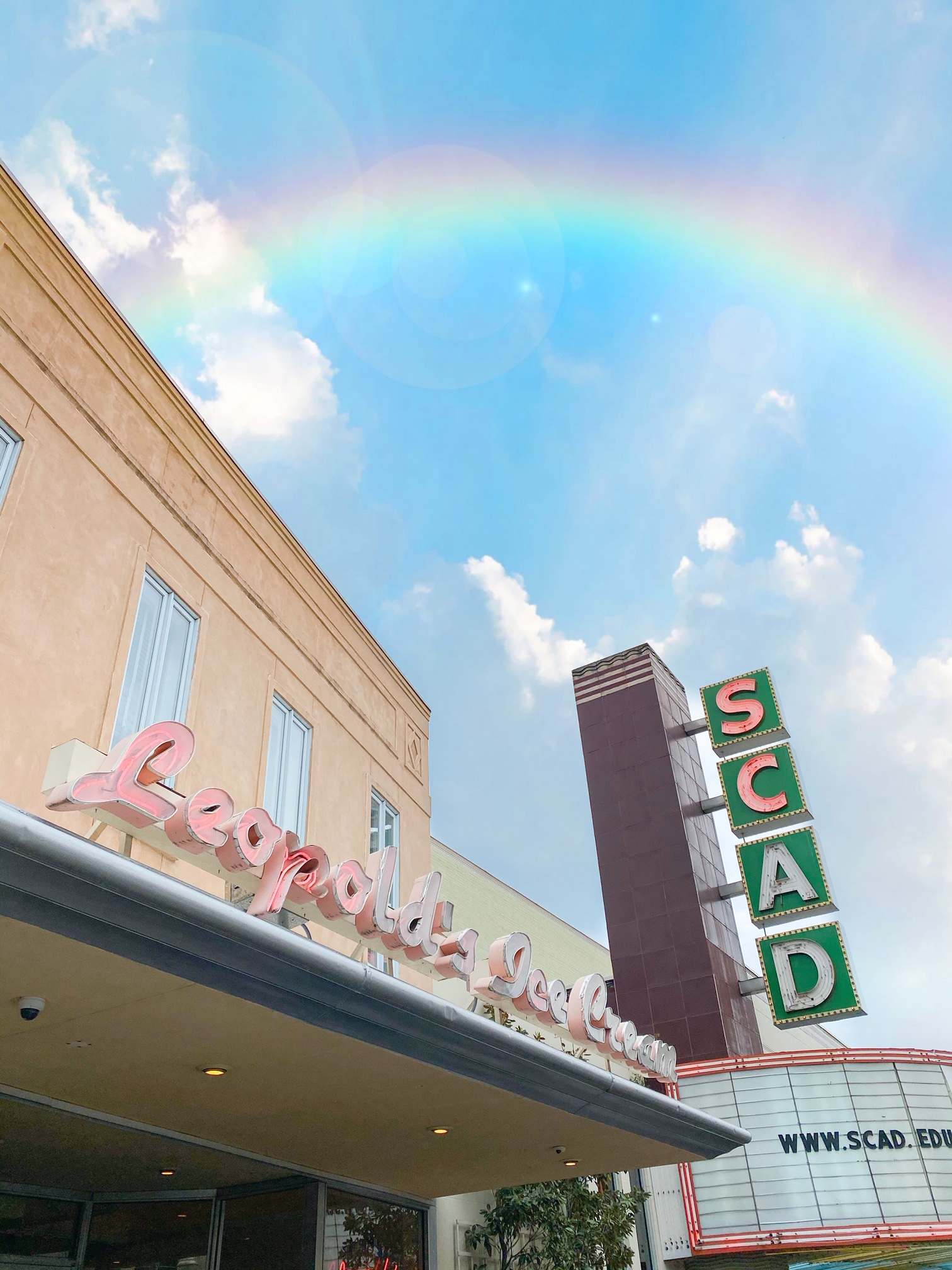 A photo looking up at the neon pink sign outside of Leopold's Ice Cream, an ice cream parlor in Savannah Georgia. The sign is very retro and has a 50's style to it. Next to the ice cream parlor, there is a sign for a SCAD theater which is also a neon sign. It is a sunny day and there is a rainbow in the sky.