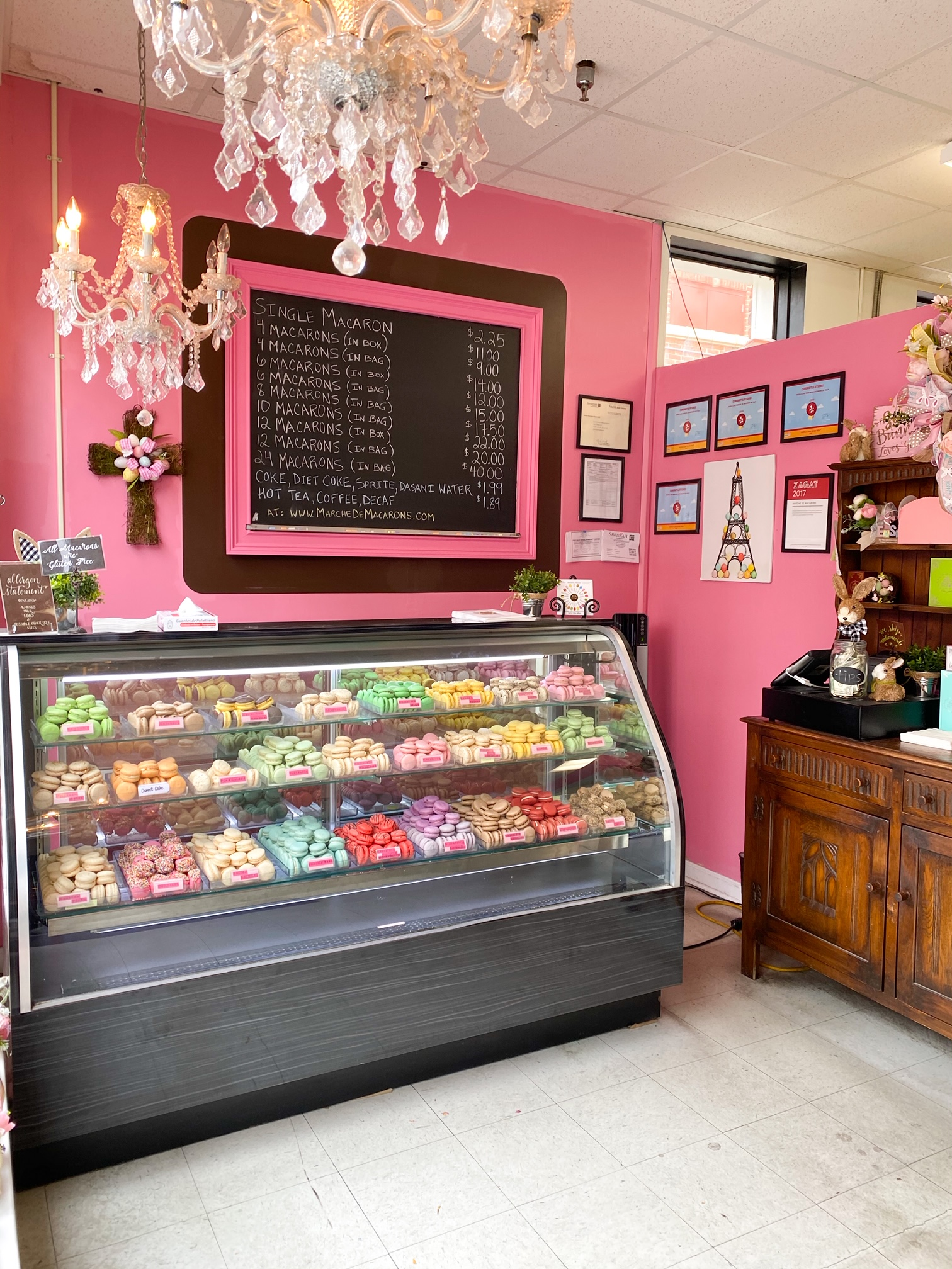 The interior of the Marche de Macarons shop in Savannah. The walls are painted bright pink and there is a large chalkboard with a pink and black frame that lists the menu for the macarons. There is a large refrigerated display case full of macarons of literally every color.