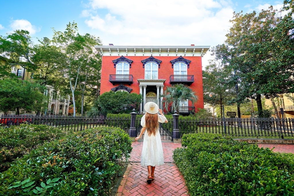 A woman standing on the sidewalk in front of the Mercer Williams House. The woman is wearing a white sundress, has long hair, and is wearing a white sunhat. She is standing on a brick sidewalk or courtyard surrounded by boxwood shrubs. The house has a black wrought iron gate, a front yard with more boxwood shrubs, and trees. The house is square with a brick façade, large arched windows with intricate black trim, and small balconies on two of the windows.