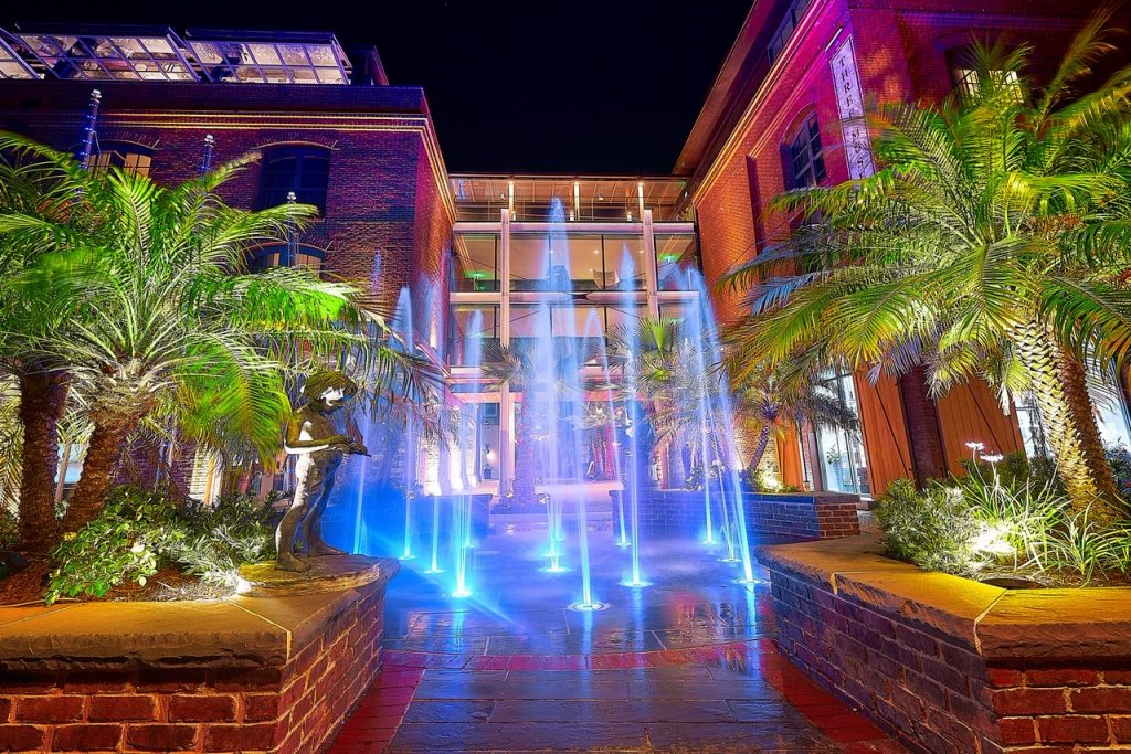 A water feature in the sidewalk in front of a large building in front of the New Plant Riverside District in Savannah. It is night time and the water feature is fountains that shoot up from the sidewalk and have colors around them. There are two raised plant beds that have greenery, palm trees, and sculptures in them. The building behind the water feature is made of brick and looks like a hotel.
