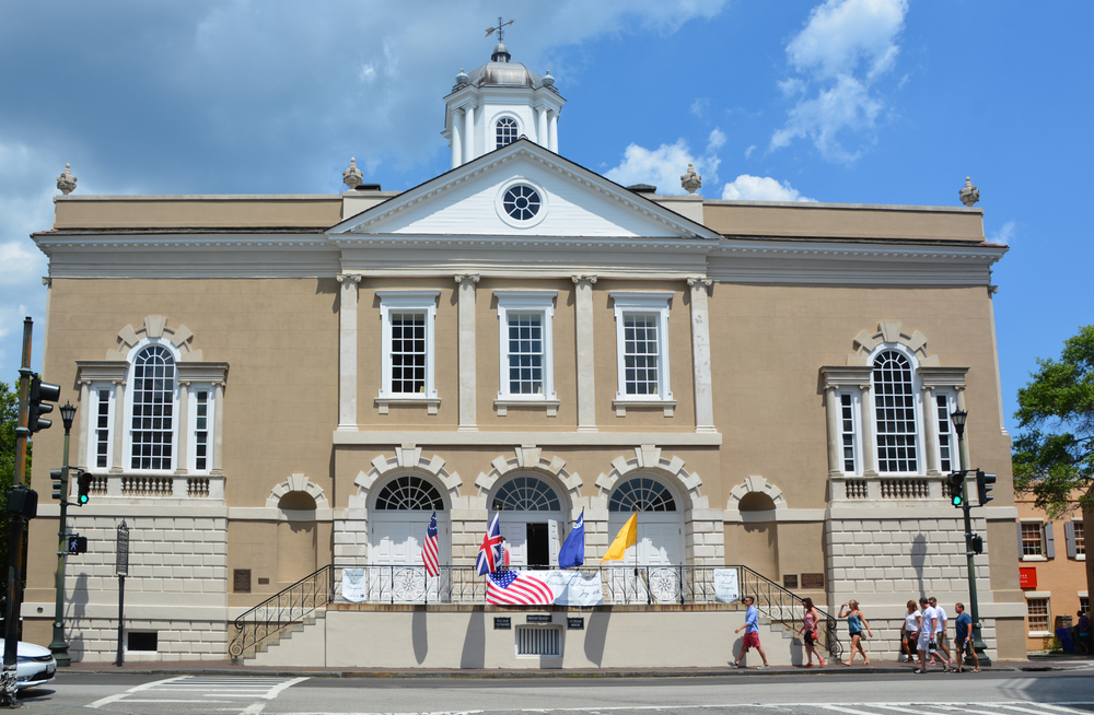 The exterior of the Old Exchange and Provost Dungeon in historic South Carolina. The building is tan and a colonial style with flags on the steps in front of it.