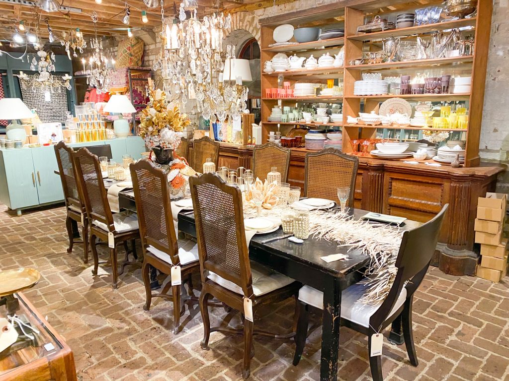 The interior of the Paris Market in Savannah Georgia. The main space is a long antique table with antique chairs. The table is elaborately decorated with glassware, a table runner, and dishes. In the background are cabinets full of dishware of all colors, trinkets, and lamps. There is also large glass chandeliers hanging from the ceiling and the floors of the store are brick.
