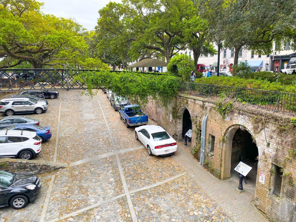An old sunken parking lot in the historic district of Savannah Georgia. It looks very old with cobblestone and no real parking spot lines. There are cars neatly parked in the middle and on the side. On the side, there are two arch ways leading to what looks like a tunnel. Each archway has an infographic stand in it. There is grass and greenery over the tunnel and over a wrought iron bridge that crosses the sunken parking lot.