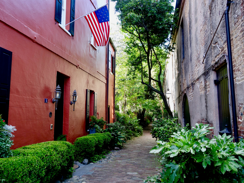 A narrow cobblestone alley with shrubs and trees in it. There are two buildings on either side, one is painted red, and the other is brick and plaster.