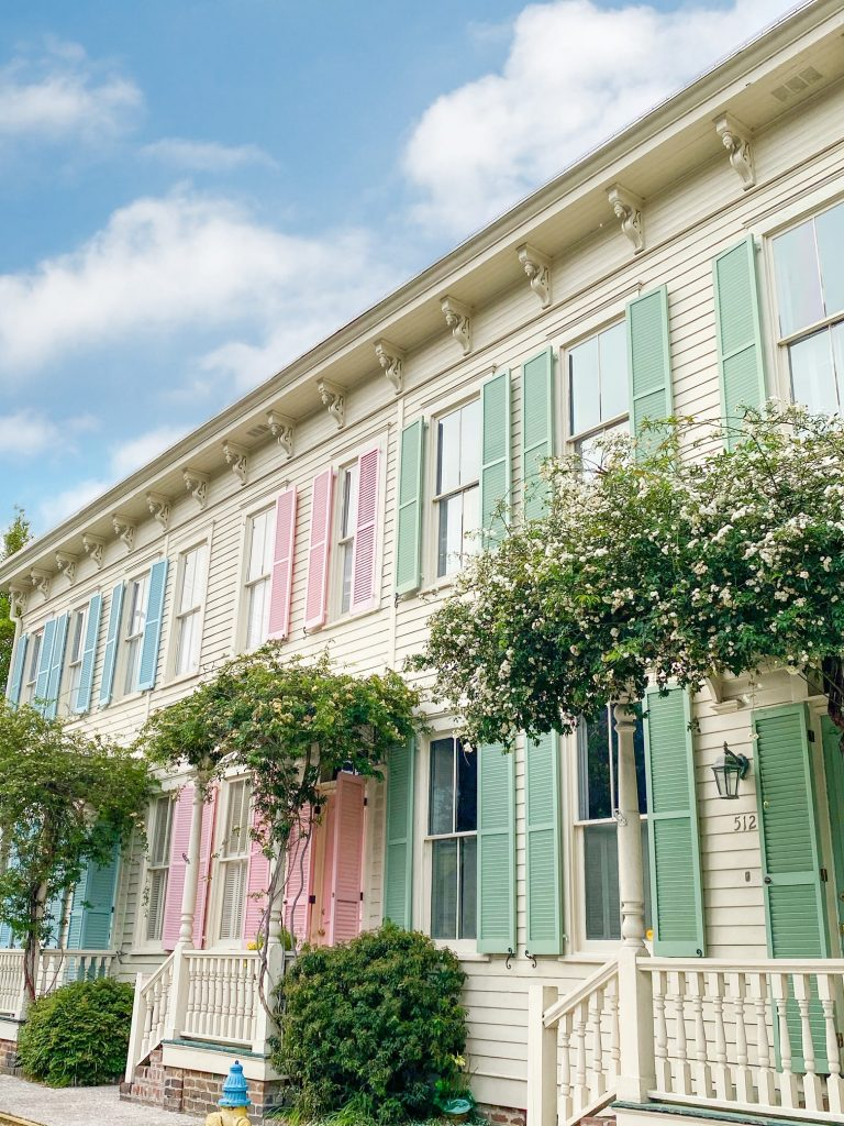 A small section of cream homes with pastel blue, pink, and green shutters on the windows and doors. It is known as Rainbow Row in Savannah Georgia and there are small shrubs and white-flowering trees outside of the homes.