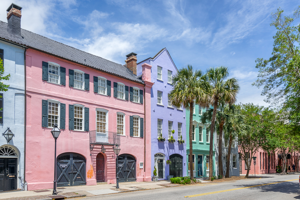 Pastel colored homes on a street in downtowns Charleston. The homes are painted pastel blue, pink, purple, teal, and a terracotta color. There are palm trees and a pretty blue sky. One of the best places to see during a weekend in Charleston.
