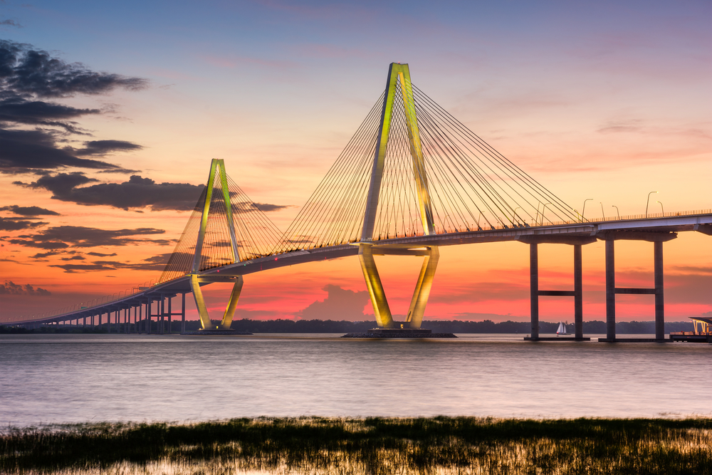 The Ravenel Bridge in South Carolina at sunset. It is a large bridge with two triangle shaped towers that have wires coming from them down onto the bridge.