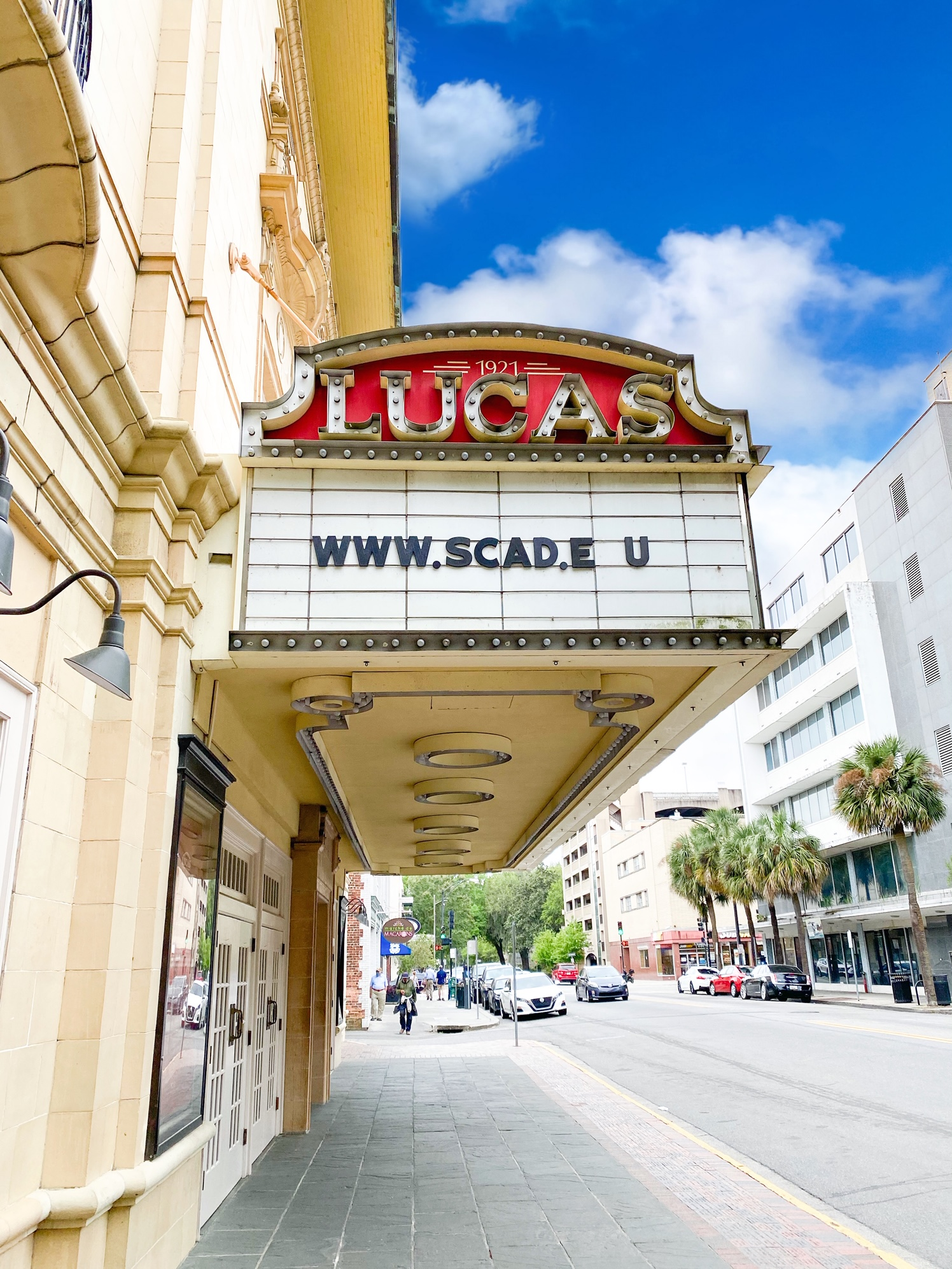 The exterior of a historic theater in Savannah Georgia. It has an antique marque out front that has the theater name 'Lucas' on it with a classic red back ground. The marque reads 'www.scad.eu'. The building itself has an Art Deco design and is a creamy color.