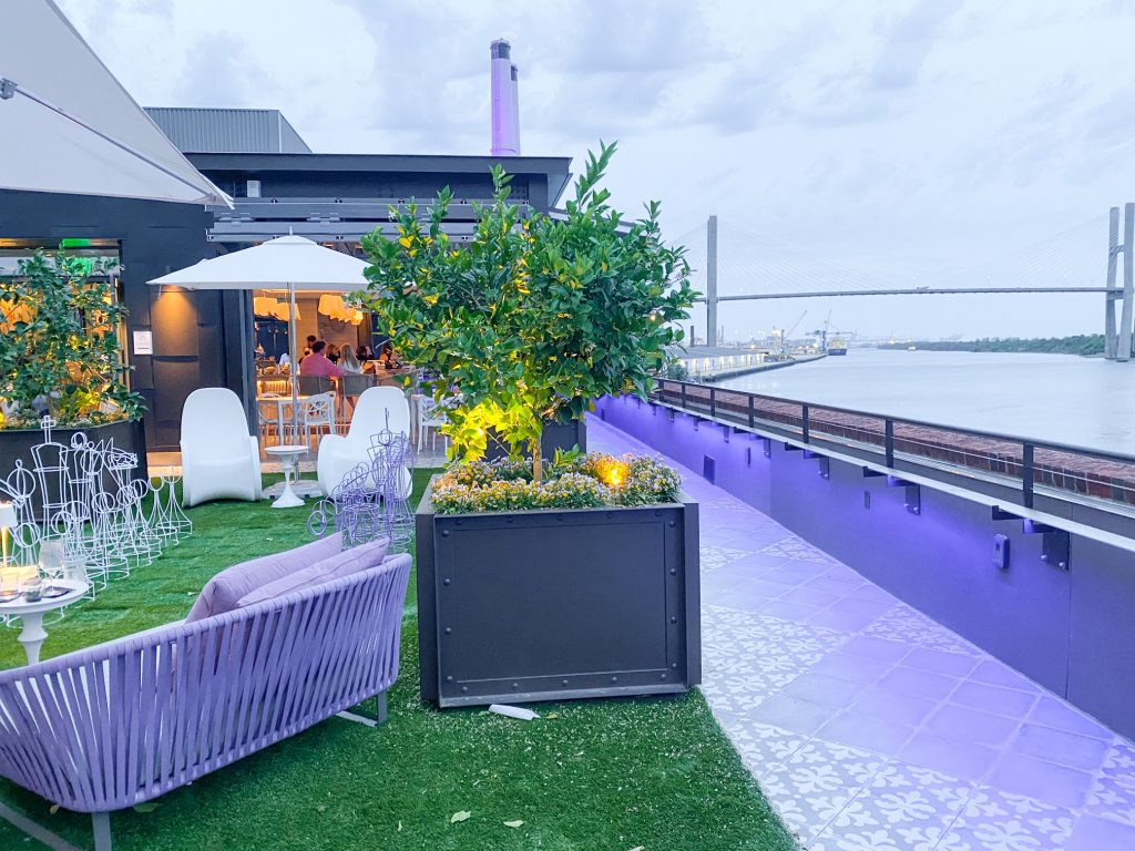 The Myrtle and Rose Roof Top Bar in the New Plant Riverside District of Savannah. It has a view of the river and is decorated in purple and white. You can see the walls and floors of the roof are painted purple, there is a purple bench, and white seats under a white umbrella. There is also fake grass on the roof top where there is a wire metal white and purple chess set. On the rooftop there are planter boxes with small plants and shrubs. You can see the entrance to the indoor bar area at the end of the rooftop. A fun Savannah photo stops