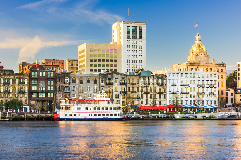 The Savannah city skyline on a sunny day. It has a mixture of old and new buildings along the river. You can also see the river and a red and white Paddlewheeler docked in front of the buildings on the river.