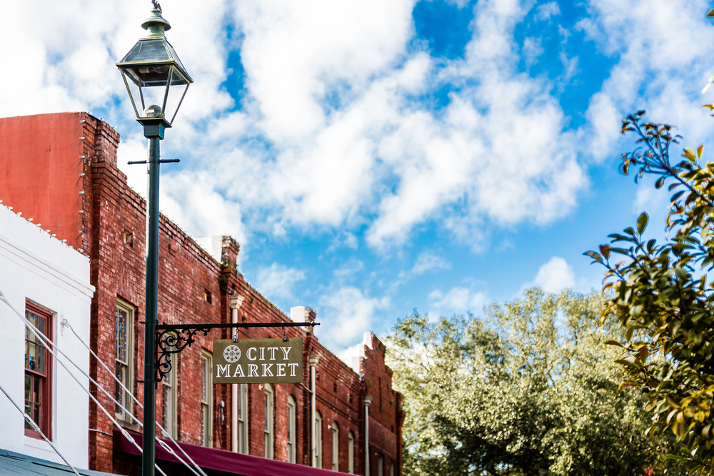 A old sign saying city market on a lamppost with building in the background. City Market is a great place for shopping in Savannah